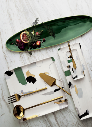 "Spot-on trending, with the so-of-the moment emerald jewel tone combined with black and gold on white. The oval platter square and rectangular shapes from Crate and Barrel are so hip on the holiday table. The CB2 Art collection is inspired by Danish modern design ""with a sense of imperfection."" Shiny white stoneware is a blank canvas, designed by Holly Addi, with abstract decals in varying shapes and brushstrokes in light purple, blue, gold, black and emerald green hand-painted on the surface. The jewel-toned cast aluminum oval platter is shiny gold (cast aluminum with electroplated finish) on the bottom and green enamel on top. It's slightly transparent and super reflective, which adds bright pop."