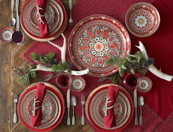 Tile motifs may have inspired these mezze plates, whose name conjures images of appetizer-centric meals. The predominantly red-patterned dinnerware (also available in tones of blue) is a natural for the Christmas table, paired with a textural red jacquard throw, inspired by antique designs, and red napkins with polyresin white antler napkin rings. Available at Pottery Barn.