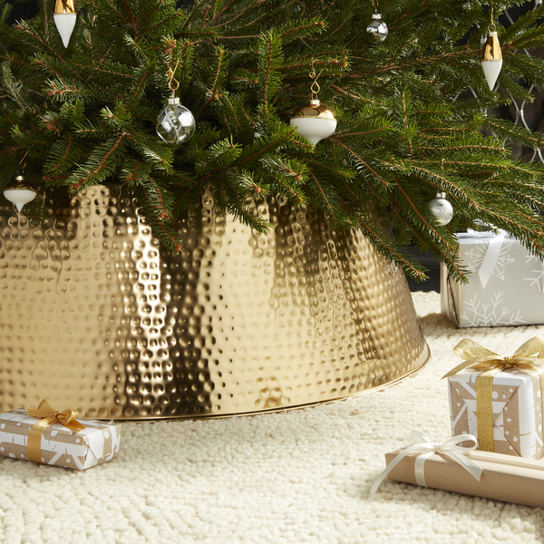 Instead of a tree skirt, a hammered brass collar dresses the base, handling the cover-up in a tailored, modern way. It's available at Crate and Barrel.