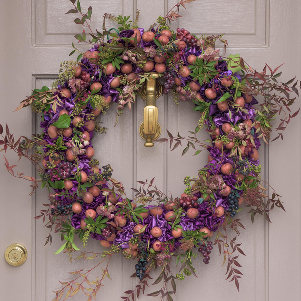 Laurie Dowling, who has created floral designs at the White House, likes the unexpected teaming of red potatoes, grapes and variegated nandina (barberry) foliage in soft shades of pale plum, purple and taupe, and tucked-in satiny orchid ribbons all creating a vintage mood set off against a Farrow & Ball painted door.