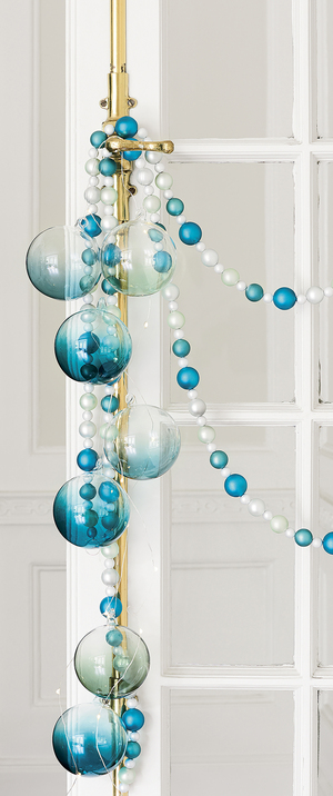 Tonal turquoise glass and plastic ornaments strung on flexible metallic garland are striking in a swag over a door.