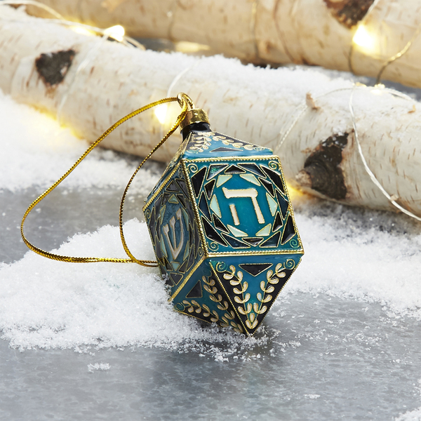 This ornate spin on the traditional Hanukkah dreidel highlights the ancient craft of cloisonne, a metalworking technique that originated in the Near East. Enamel inlays within delicate wire strips create the patterns. Each side bears a letter of the Hebrew alphabet: nun, gimel, he and shin. Hang the turquoise dreidel as an ornament or make it a part of a Hanukkah table scape.