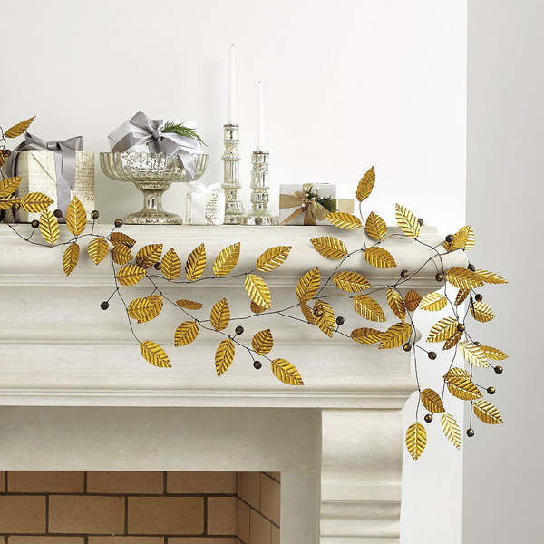 The simplicity of these glittery gold branches makes decorating almost effortless on a creamy mantel. The gilded leaf garland is artisan-crafted with beautifully detailed leaves accented with berries on flexible iron wire at Ballard Designs, which recommends tucking in with fresh greenery or setting it on a table with votives.