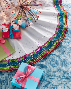 A tree skirt with a party attitude: The crisp white polyester taffeta is scattered with silver beads and edged with colorful beaded ribbons as well as one in velvet. The 64-inch skirt is part of Kim Seybert's Playful Brights collection.