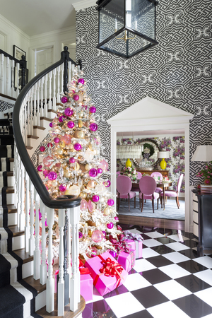 Graphic wallpaper and a classic black-and-white porcelain checkerboard floor are the backdrop for a tree decked out in a mix of gleaming hot pink, pink, gold and silver ornaments. The pinks pick up hues from the azalea velvet chairs in the adjacent dining room, which also has pops of chartreuse in cascading bouquets on Clark & Clark wallcovering. The metallic accents add a touch of formality to the playful choice.