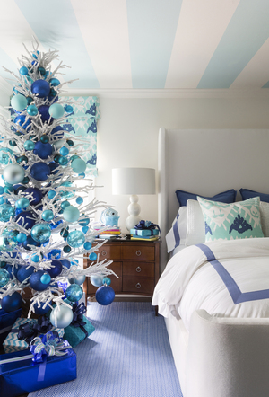 Designer Tobi Fairley pulled hues from her pre-teen daughter Ellison's bedroom to decorate the skinny white branched retro tree with vivid shades of blue, from rich indigo to pale aqua, in ornaments of different scales. The aqua picks up from the glorious wide-striped ceiling.