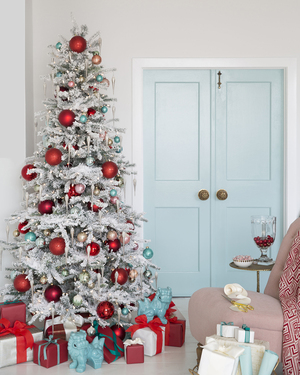The Mine's style director, Eddie Ross, fashioned this retro-feel flock tree with a modern millennial twist, decorating it with overscale ornaments in red and turquoise. He used a stronger shade of turquoise in foo dog statues that keep company with coordinating brightly wrapped packages beneath.