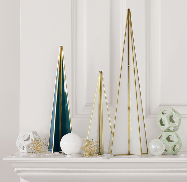 Sleek glass trees trimmed in copper create a modern silhouette on a traditional mantel, foyer tabletop or sideboard. The triangular shapes in teal, mint or milk glass come in a choice of 4 1/2, 6 1/2 and 21 inches tall. The Flash trees are a CB2 exclusive. Faceted open ceramic balls in shiny mint or matte white also are available.