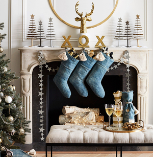 Simple, familiar, homespun: A trio of denim stockings with white tassels hang by the fire. It's an American classic, set in a traditional living room with stone fireplace and picture moldings on the wall. The pieces are part of a collection by stylists and fashion designers Emily Current and Meritt Elliott for Pottery Barn. It includes X-and-O aluminum holders with powder-coated brass finish and tasseled wine bags in denim-y double-slubbed cotton. The stockings have sold out, but other pieces still are available.