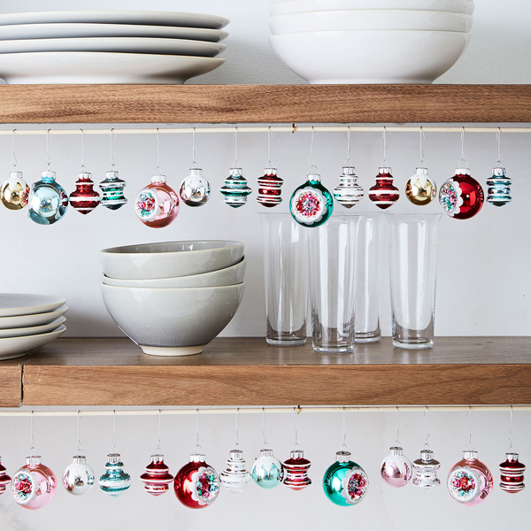 A re-creation of mid-century style by Shiny-Brite, whose signature round ornaments of colorful glass and painted pastels were first created just before World War II. The vintage-inspired collection of bright 1 3/4-inch-diameter ornaments was created exclusively for West Elm. Here is an unexpected display: strung on skinny white tension rods at the base of shelves.