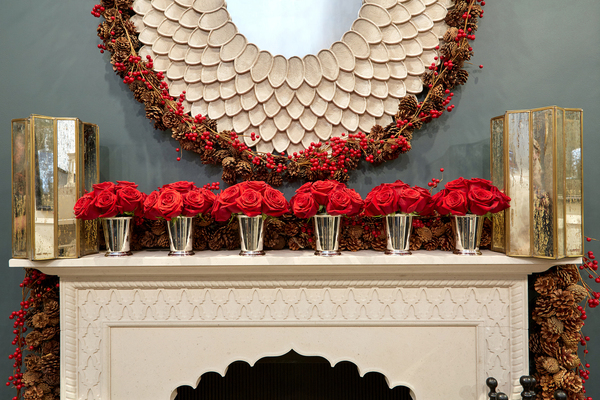 Alexa Hampton decorated the new Moorish-influenced honed limestone Castello mantel she designed for Chesney's with five simple shiny silver vessels filled with red roses. Draping the back is a garland of pine cones and red berries, which also borders the 40-inch carved Chloe mirror in pearlescent finish from The Mines.
