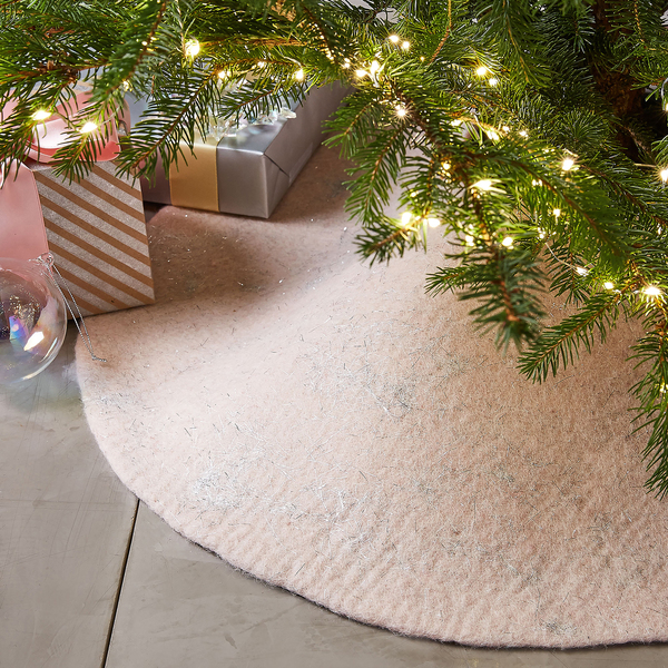 In the color of the moment, a 33-inch blush hand-felted wool tree skirt from West Elm dances as light reflects in its metallic threads.