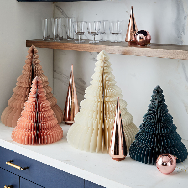 Paper accordian tabletop trees in au courant shades of apricot, cream and charcoal are cut, shaped and folded by hand. Shiny glass trees finished in copper combine for a stylish display. One plus for the paper pieces: They fold and take up little space after the holiday.