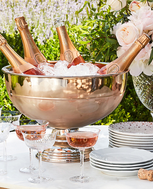 Bridal and fashion designer Monique Lhuillier is ringing in the new year with her signature rosy-gold accessories, like this copper Margot champagne bucket, part of her fall collection for Pottery Barn. Also included: cut soda lime coupes, white porcelain ware and stacks of appetizer stoneware plates imprinted with tiny metallic hearts sprinkled on like confetti.