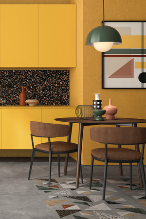 """Contrasting sizes and styles is popular with terrazzo looks. With ABK's Blend, the dark confetti-like terrazzo called Play on the back wall is paired alongside a concrete-look floor featuring a """"carpet"""" inset with geometric shapes filled with multicolored terrazzo."""